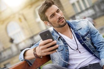 Trendy guy in town using smartphone and handsfree device