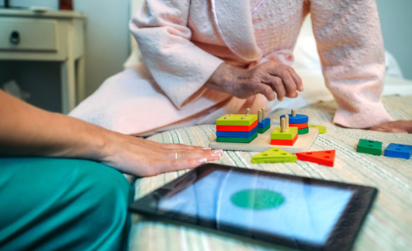 Female doctor showing geometric shape game to elderly female patient with dementia
