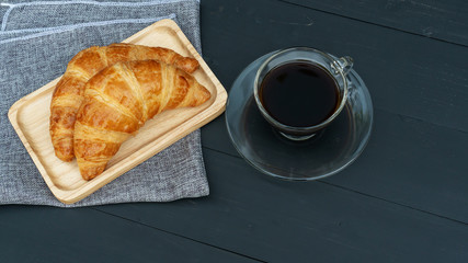 Croissant and black coffee on a black wooden table.