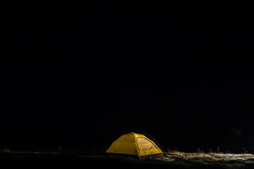 Spoed Foto op Canvas Kamperen Camping for a starry night. The tent glows under a night sky full of stars. Milky way. leisure tourists. for friends. the first snow. the journey, autumn