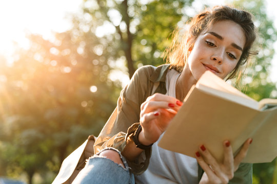 Image of young woman smiling and reading book in green park
