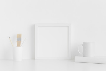 White square frame mockup with workspace accessories on a white table.
