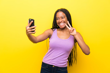 African American teenager girl with long braided hair over isolated yellow wall making a selfie