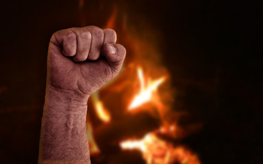 Raised clenched fist with burning flames from bonfire in background. Stock photo with socialism, communism, revolution, workman and power to the people concept