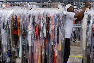 "A worker moves clothing in the storage area at Rent the Runway's ""Dream Fulfillment Center"" in Secaucus, New Jersey"