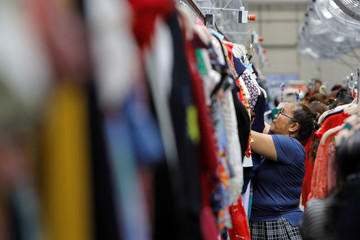 "A quality control worker hang clothing at Rent the Runway's ""Dream Fulfillment Center"" in Secaucus, New Jersey"