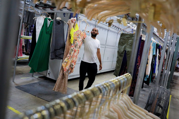 "A worker retrieves clothing from the steam tunnel at Rent the Runway's ""Dream Fulfillment Center"" in Secaucus, New Jersey"