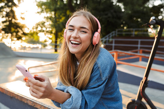 Positive young teenage girl outside in park holding mobile phone.