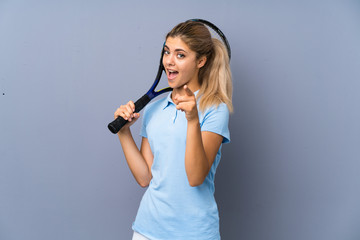 Teenager tennis player girl over grey wall surprised and pointing front