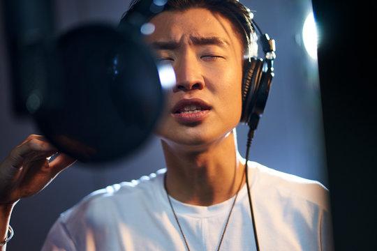 young asian singer singing in recording studio