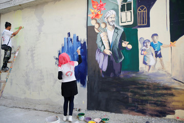 "A group of artists, who call themselves ""The Art Revolution Team"" paint a mural inside the alleys of old Mosul"