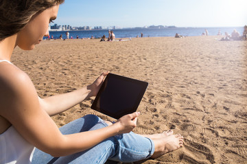 Female online checking e-mail via portable digital gadget while sitting on sand on the beach in sunny summer day during free time. Hipster girl watching video via touch pad, relaxing near sea