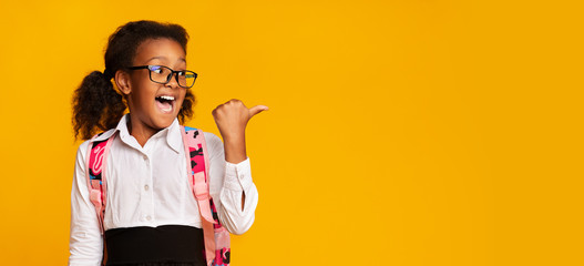 Excited Black Schoolgirl Pointing Thumbs At Copy Space In Studio