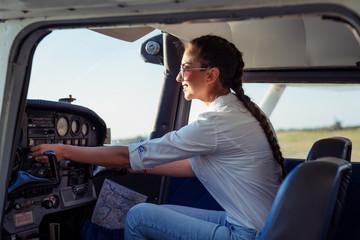 Fototapeta Female pilot preparing for a flight in a light aircraft obraz
