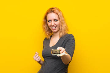 Young woman over isolated yellow background taking a lot of money