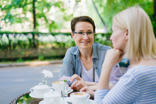 Attractive adult women friends blonde and brunette are speaking in outdoor cafe sitting at table with drinks. Conversation, friendship and people concept.