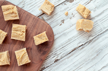 Squares of delicious, homemade peanut butter fudge over a rustic wood table background. Image shot from top view.