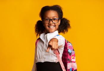 African American Schoolgirl Pointing Finger At Camera, Studio Shot