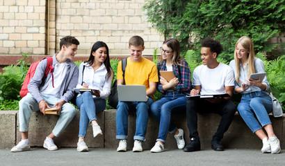 Happy teens preparing for exams in university campus