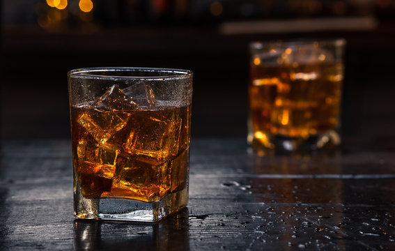 Two Glasses of Whisky (whiskey), bourbon, ice tea or coke (cola) soda with ice and water drops on wood table at dark background with copy space, close up