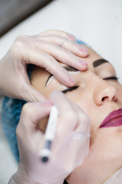 Decorative cosmetology. Closeup of female beautician hand applying eyeliner to create contour.