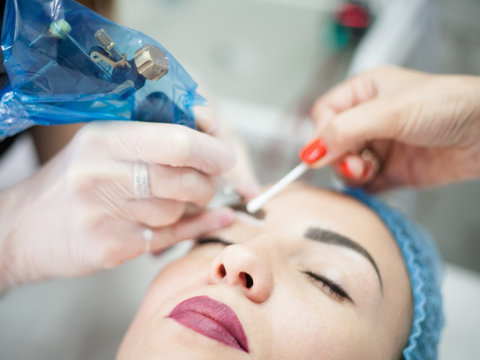 Decorative cosmetology courses. Female beautician using tattoo machine for eyebrow microblading.
