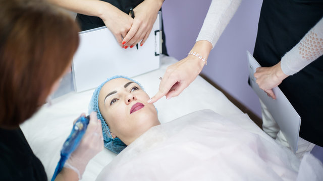 Decorative cosmetology. Professional skin treatment. Ladies learning new permanent makeup technique, lip coloring.