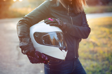 Woman in leather jacket holds motorcycle helmet