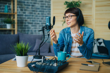Attractive young lady blogger speaking in microphone gesturing sitting at table in studio using...