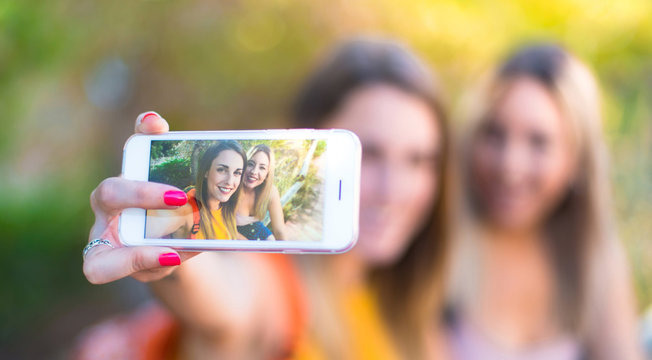 Young student girls with backpack in a park making a selfie