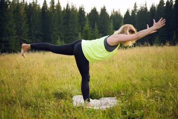 Woman doing yoga outdoors in summer