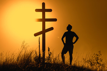 Man near orthodox cross on the background of the sunset
