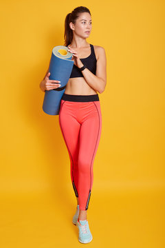 Full length portrait of beautiful athletic young woman holding yoga mat in hands, looking aside, ready for working out, sporty female posing isolated over yellow background. Fitness concept.