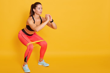 Close up of athletic woman in squat in gym, fit girl exercising with resistance band for lower body relief, sporty lady wearing sport clothes and sneakers posing isolated over yellow studio background
