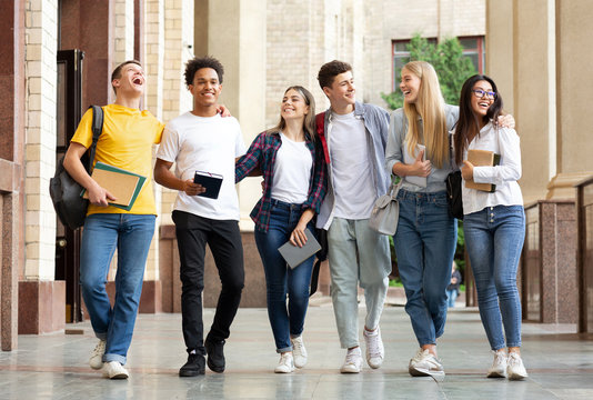 Multiracial students walking after classes in university campus