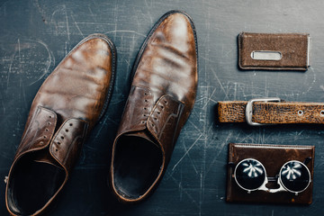 Leather accessories, brown shoes, passport cover, belt and sunglasses. Travel concept.