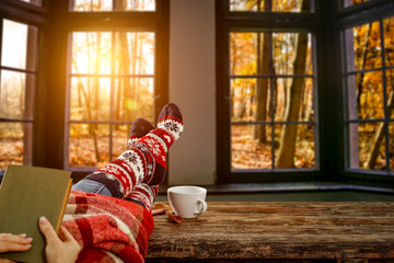 Slim young woman legs and autumn window background