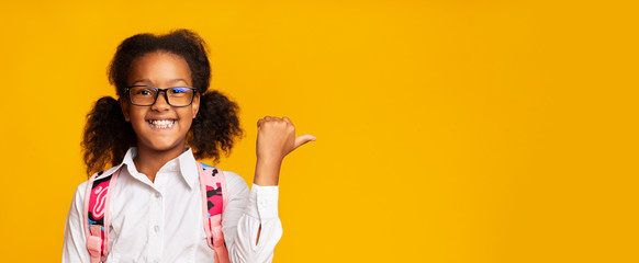 Afro School Girl Pointing Thumbs At Copy Space, Yellow Background