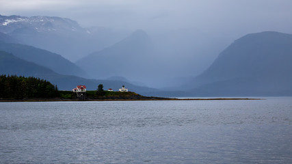 Point Retreat Lighthouse, Juneau Alaska. Early on a foggy morning snow on mountains in the background.