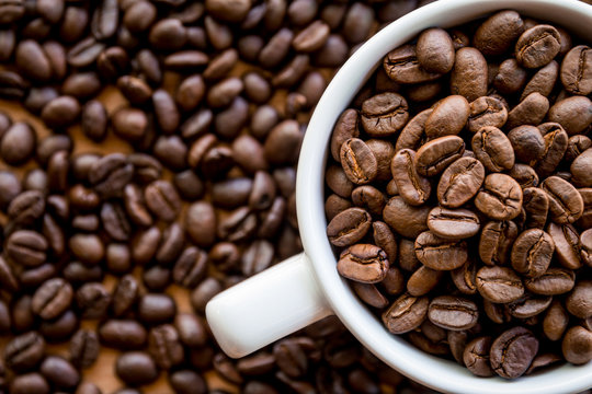 Coffee beans full in white coffee cup background