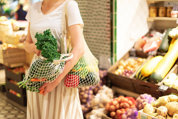Zero waste concept with copy space. Woman holding cotton shopper and reusable mesh shopping bags with vegetables, products. Eco friendly mesh shopper. Zero waste, plastic free concept.