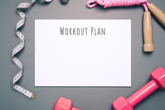 Flat lay shot of workout plan on gray background.
