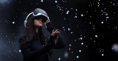 Wall Mural - Beautiful woman with flowing hair in futuristic dress over dark background. Girl in glasses of virtual reality. Augmented reality, game, future technology concept. VR.