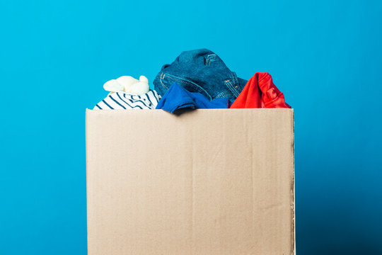 Cardboard box with things on a blue background. Donation concept