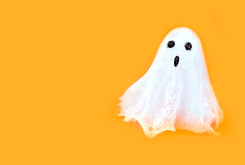 Halloween white spooky ghost spirit on orange backgrounds. Minimal concept scary autumn.