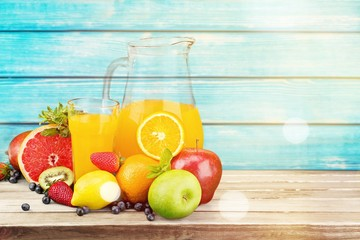 Tasty fruits and juice with vitamins on background