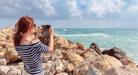 Attractive mature traveler woman use mobile phone take a photo of beautiful seascape.