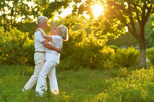 Portrait of happy beautiful senior couple dancing in summer park