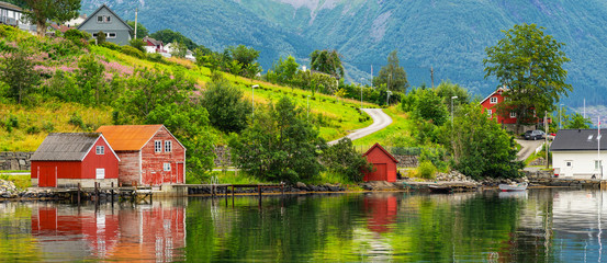 Wall Murals Northern Europe Norwegian rural wooden houses green coast of fjord, landscape sea view, Norway, Rosendal.