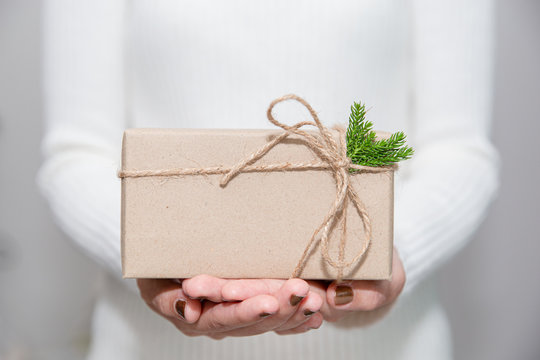 Woman hands with white sweater holding a diy gift box for special event with copy space.